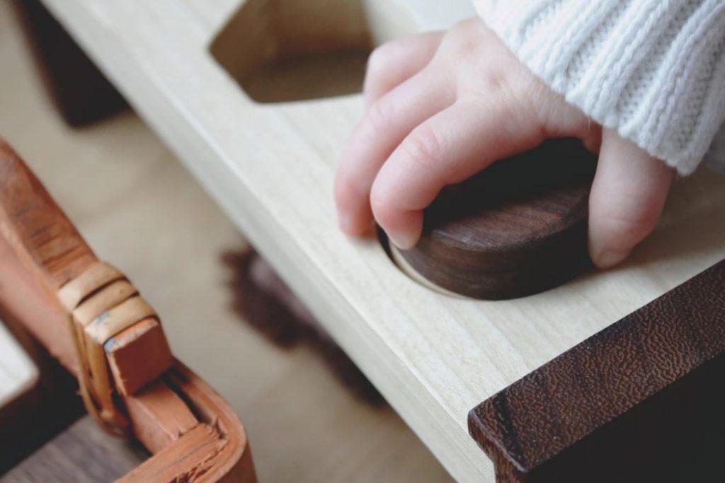 Colegios Montessori: niño jugando en escuela infantil con material de resaques de madera.